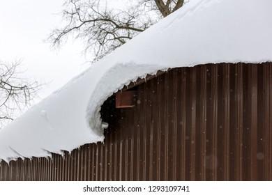 huge snow block hangs from the roof of metal hangar. snow cornice