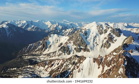 Huge snow mountains. View from the top of the drone. In places, you can see small people climbing to the top. Panorama of steep peaks and rocks, snow cornices. Mountaineering class. Extreme rest.