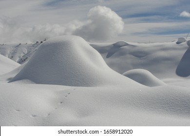 Huge snow-white snowdrifts with snow sparkling in the sun in the mountains of Georgia