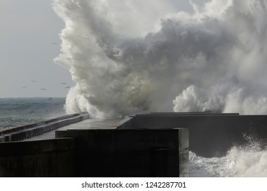 Huge splash closeup from a wave breaking over a pier. North of Portugal.