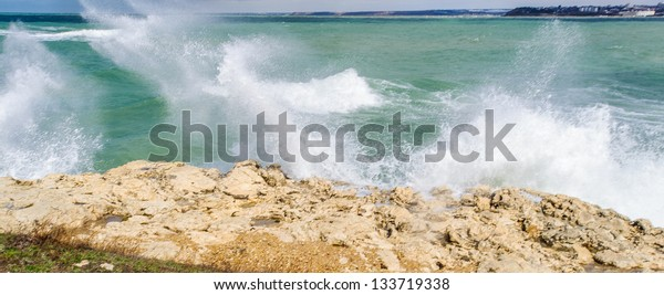 Huge splash of the wave of the sea crashing over the rock