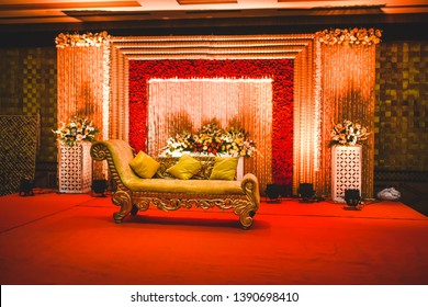 Huge stage at a wedding ceremony with beautiful yellow sofa for bride and groom. floral background lit by multiple stage lights.