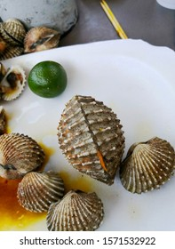Huge steamed cockle on a plate with calamansi and satay stick on the background.