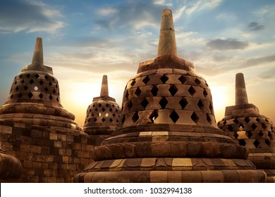 Huge stone Buddhist stupas against the background of the sunrise in the Borobudur Temple.  Java island. Indonesia. Famous historical place. Outside. Religion concept.