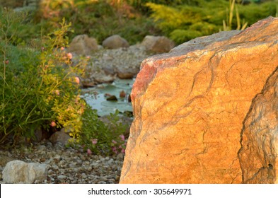 Huge stone and decorative garden pond at sunset