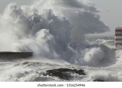 Huge stormy wave splash. Douro river mouth pier and beacon.