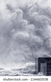 Huge stormy wave splash over a pier. Converted black and white.Toned blue.