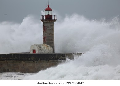 Huge stormy waves over old lighthouse and granite pier