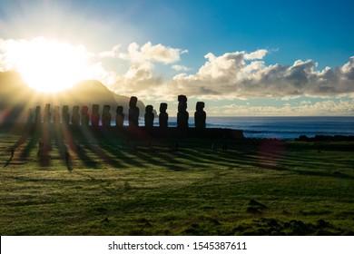 Huge sun ray lights behind Ahu Tongariki moais at dawn in Rapa Nui