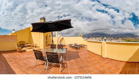 Huge  sunny terrace of a summer holiday property with hanging chair, table, umbrella, sun beds, bamboo sofas and sea view.