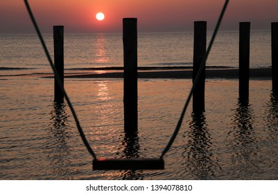 A huge swing set in the poles village. A beautiful sunset at the background. Sunset in the Netherlands