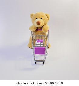 Huge teddy bear pushing a shopping cart, on a white background, from the front