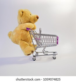 Huge teddy bear pushing a shopping cart, o a white background, from the side