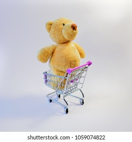Huge teddy bear standing in a shopping cart, on a white background, at an angle