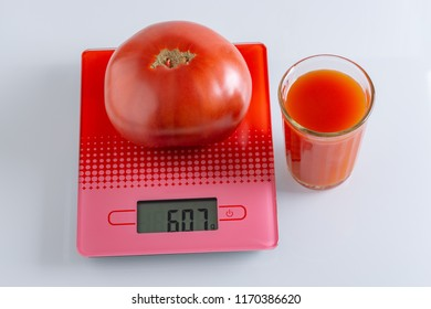 Huge tomato on scales and a glass of tomato juice