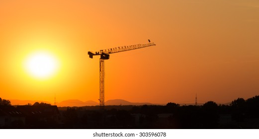 Huge tower crane silhouette shot against an incredibly colorful sunset over the hills of the Black Forest, Germany