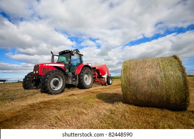 huge tractor collecting haystack in the field in a nice blue sunny day