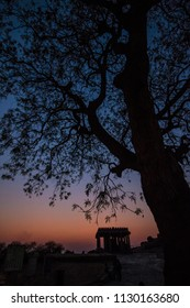 Huge tree silhouette witht a beautiful sunset and an ancient temple ruin in south India