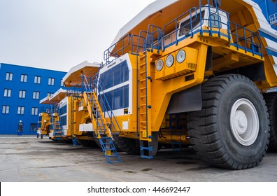 Huge Trucks BelAZ In A Row. Zodzina, Belarus - March 9, 2016: Huge haul yellow colored Trucks byBelarusian manufacturer BelAZ (up to 360 metric tons). Trucks in a Row and are ready for the hard work.