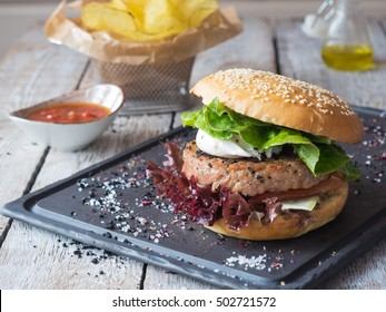 Huge Tuna steak burger with poached egg and potato chips on a black boad. wooden background