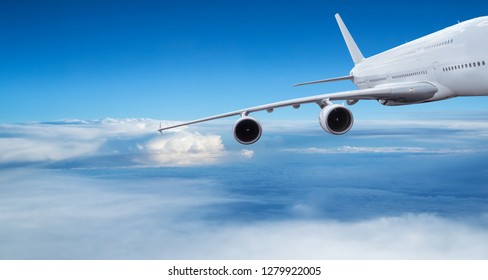 Huge two-storey passengers commercial airplane flying above dramatic clouds. Travel and business concept.