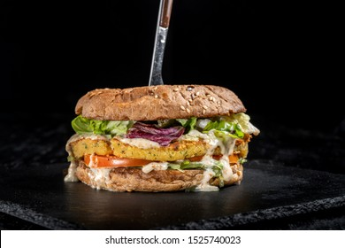 Huge veggie burger with potato patty, salad, cheese. Laid out on black slate.
