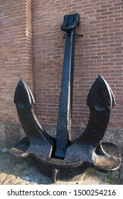 A huge vintage black metal anchor with two large pointed paws standing on the ground, propped up and attached to a red brick wall
