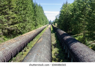 Huge Water Pipelines through Woods to a Hydroelectric Plant under Blue Sky on a Sunny Summer Day. Campbell River, BC, Canada,