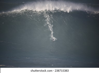 A huge wave breaking with a surfer in Nazare, Portugal.