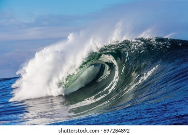 A huge wave breaks in the ocean on a sunny day.  A perfect wave for surf.