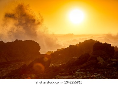 Huge wave breaks on rocky coast at sunset in tsitsikama national park, south africa