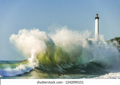 Huge wave on a beach in Biarritz city with the lighthouse in the background. Basque country of France.