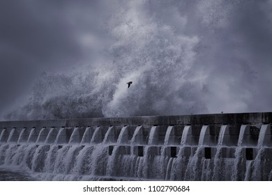 Huge wave splash in a stormy day. River mouth pier from the north of Portugal. Toned blue.