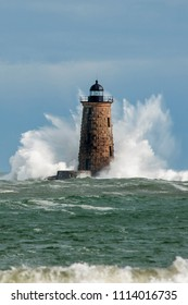 Huge waves break around the stone tower of Whalback lighthouse in Maine during rare high tide.