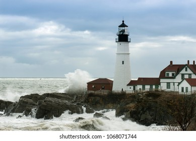 Huge waves crash against Portland Head lighthouse as sunlight breaks through storm clouds. It is the oldest lighthouse in Maine, and the second oldest in the United States.