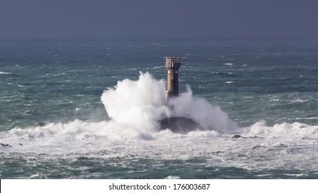 Huge waves crashing Longships Lighthouse photographed from Lands End Cornwall England UK