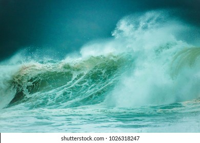 Huge waves crashing on a beach on a misty dark day with mountain in the background.