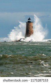Huge waves surround stone lighthouse tower of Whaleback light in Maine during a unique high tide in early Spring. Vertical orientation.