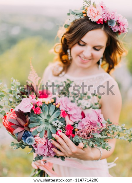 Huge wedding bouquet of colourful exotic flowers in the hands of the bride.
