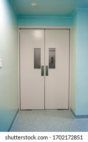 A huge white door in the white corridor in the hospital.