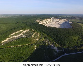 Huge white industrial lime-pit for  cement and lime production (limestone quarry) near abandoned older lime-pit on the top of wooded mountain, aerial view. Opencast mining quarry. Deforestation