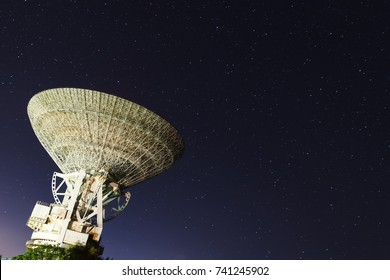 huge white satellite antenna radio telescope on the background of star at night