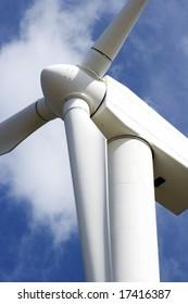huge wind turbine against a cloudy blue sky