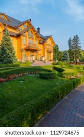 A huge wooden mansion with a landscape design under a blue cloudless sky. Konka, the residence of Yanukovych Museum of Corruption of Ukraine Mezhyhirya, Kiev