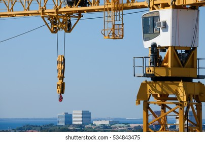Huge yellow building construction crane with hook, pulley, lattice boom and cabin with an aerial view of a city and blue water bay.
