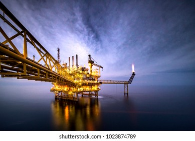 A huge yellow of offshore oil rig drilling platform in the gulf of Thailand at night time,Process platform for production oil and gas,Petroleum production and exploration industrial