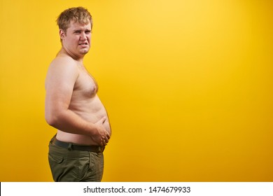 Huge young man with big fat belly and naked body in profile. Concept of obesity, fast and junk food, sports, liposuction, weight loss with free space for your product or text