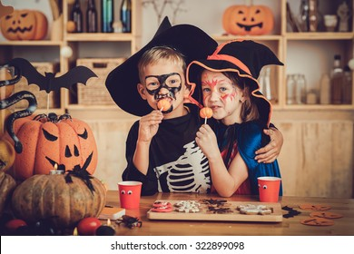 Hugging boy and girl enjoying sweets at Halloween party