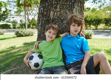 Hugging brothers sitting under the tree after playing soccer