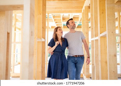 Hugging couple at construction site of their new home, dreams come true